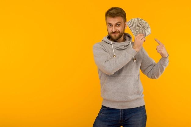 Homme Joyeux Dans Un Sweat à Capuche Gris Pointe Un Doigt Sur Des Dollars D'argent Sur Fond Jaune Photo Premium