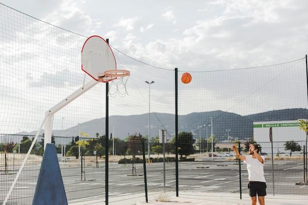 Homme, lancer, basket-ball, dans, cerceau Photo gratuit