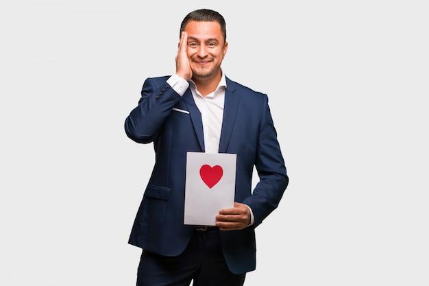 Homme latin d'âge moyen célébrant la saint valentin surpris et choqué Photo Premium