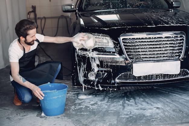 Homme lave sa voiture dans un garage Photo gratuit