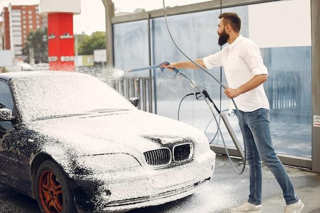 Homme lave sa voiture dans une station de lavage Photo gratuit