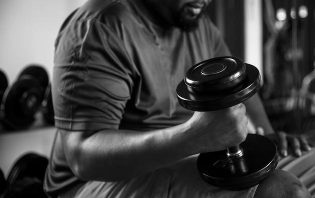 Homme levant des poids au gymnase Photo gratuit