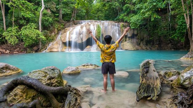 Un homme de liberté jouit avec une belle cascade dans la forêt tropicale Photo Premium