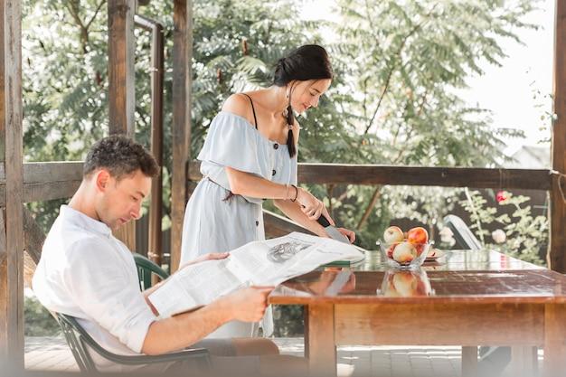 Homme lisant un journal avec sa femme coupant des fruits dans un jardin en plein air Photo gratuit