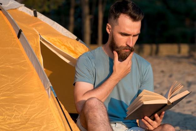 Homme lisant un livre à côté de la tente Photo gratuit