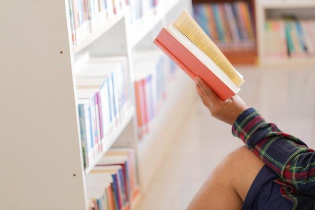 Homme lisant livre dans ses mains dans la bibliothèque. Photo gratuit