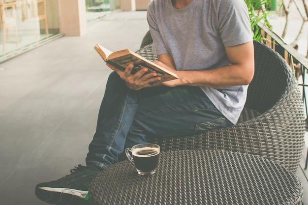 Un homme lisant un livre avec du café Photo Premium