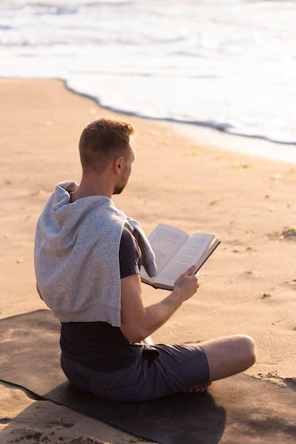 Homme Lisant Et Méditant Sur La Plage Photo gratuit