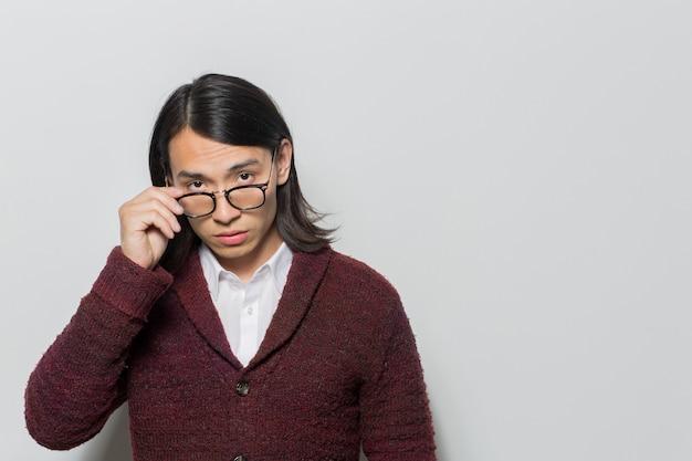 Homme avec des lunettes posant et regardant Photo gratuit