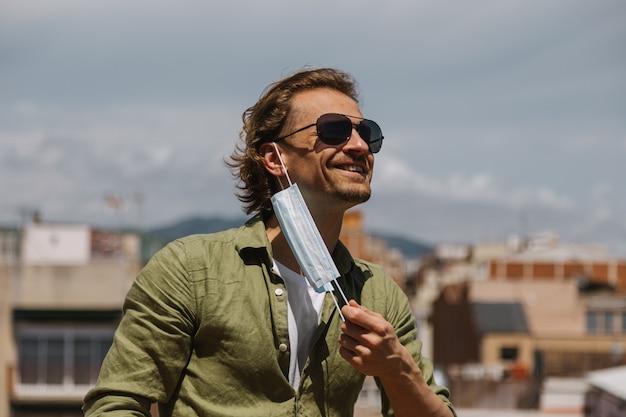 Un Homme à Lunettes De Soleil Enlève Joyeusement Le Masque Médical De Son Visage Aux Beaux Jours Photo Premium