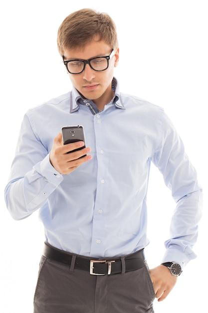 Homme à lunettes tenant un téléphone Photo gratuit