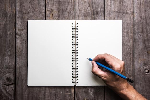 Homme main écrit dans un grand bloc-notes sur une table en bois Photo Premium
