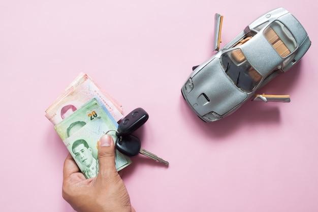 Homme, main, voiture, clé, thaï, billets, voiture, modèle, rose, fond Photo Premium