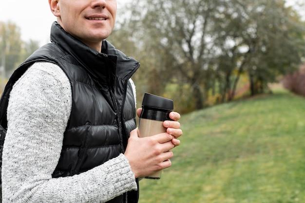 Homme, mains, tenue, thermos, nature Photo gratuit