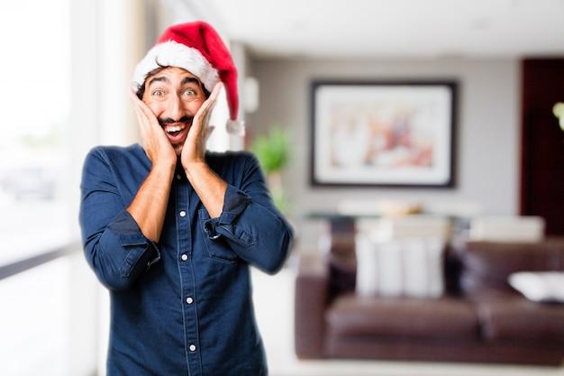 L'homme avec les mains sur le visage et le chapeau de santa Photo gratuit