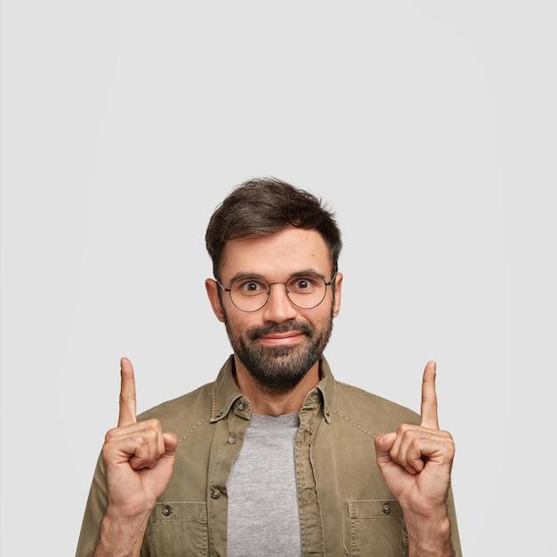 Un Homme Mal Rasé à L'air Agréable Remarque Quelque Chose D'étonnant Vers Le Haut, Des Points Au-dessus De Sa Tête Photo gratuit