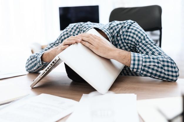 Un homme a mal à la tête. il a couvert sa tête avec des papiers. Photo Premium