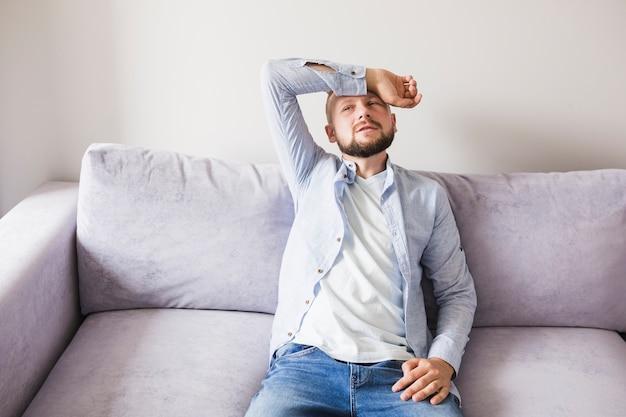 Homme malade sur un canapé Photo gratuit