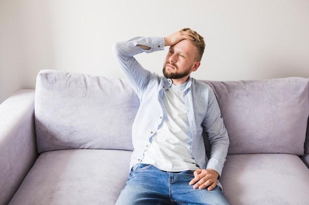 Homme malade sur le canapé Photo gratuit