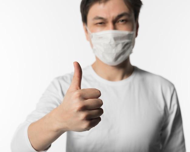 Homme Malade Défocalisé Avec Masque Médical Donnant Les Pouces Vers Le Haut Photo gratuit