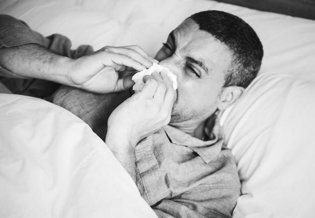 Homme malade éternuant au lit Photo gratuit