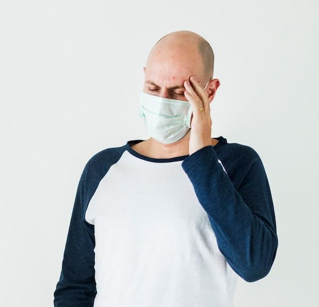 Homme malade portant un masque chirurgical ayant un mal de tête Photo Premium
