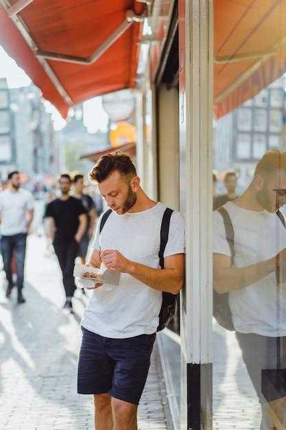Homme mangeant des gaufres hollandaises dans la rue près du café. alimentation de rue en hollande. Photo gratuit