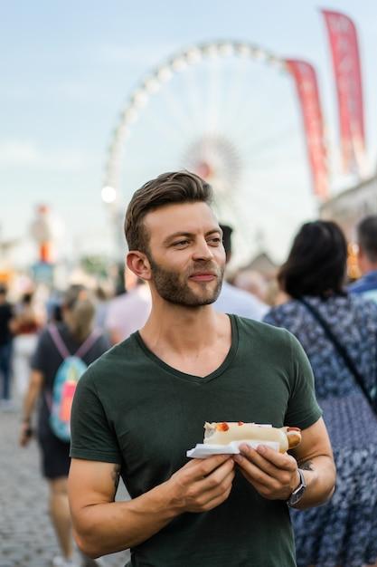Homme mangeant de la nourriture de rue. hot-dogs de rue Photo gratuit