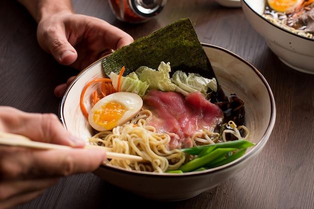 Homme mangeant des ramen asiatiques avec du thon et des nouilles dans un restaurant Photo Premium