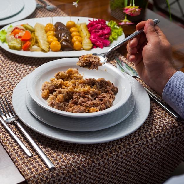 Homme, Manger, Délicieux, Oriental, Pois, Soupe, Viande, Bois, Table Vue Grand Angle. Photo gratuit