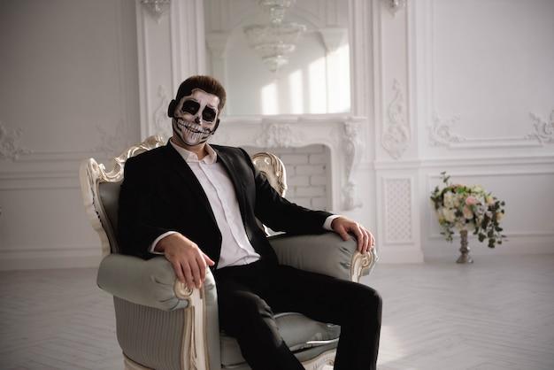 Homme avec un maquillage terrible sur fond de salle blanche. Photo Premium