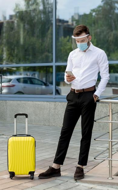 Homme Avec Masque Et Bagages à L'aide De Mobile Photo gratuit