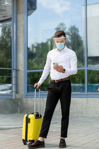 Homme Avec Masque Et Bagages Contrôle Mobile Photo gratuit
