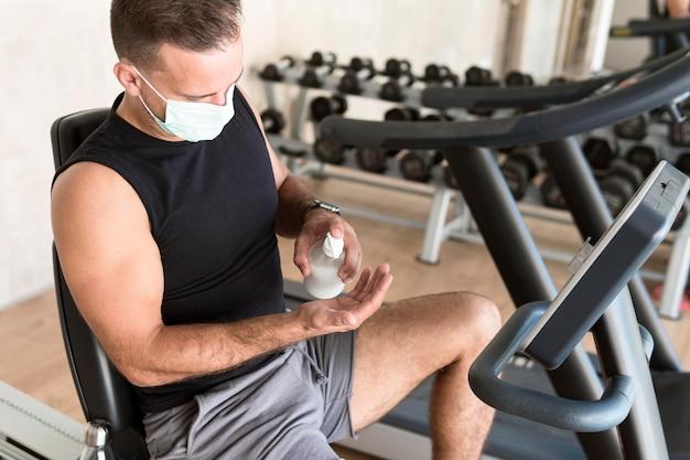 Homme Avec Masque Médical à L'aide De Désinfectant Pour Les Mains Au Gymnase Photo gratuit