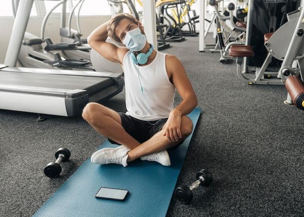 Homme Avec Masque Médical Et écouteurs à La Salle De Sport Sur Tapis Photo gratuit