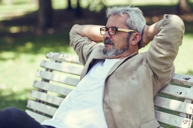 Un homme mature pensif assis sur un banc dans un parc urbain. Photo gratuit