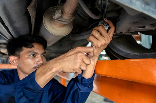 Un homme mécanicien est en train de réparer le moteur sur le pont élévateur. en utilisant des outils clés de réparation de voiture dans le garage. Photo Premium