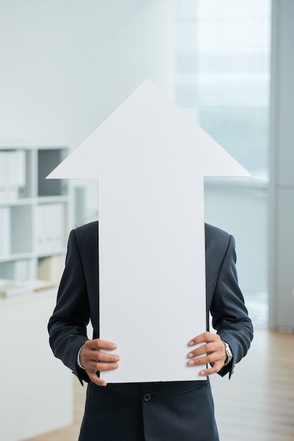 Homme méconnaissable en costume debout dans le bureau et tenant une grande flèche blanche pointant vers le haut Photo gratuit