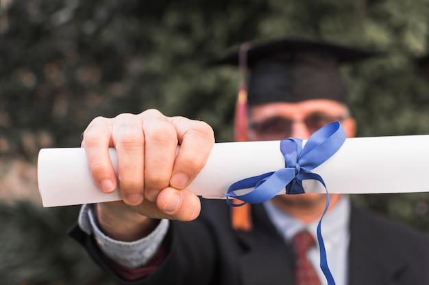 Homme méconnaissable montrant le diplôme Photo gratuit