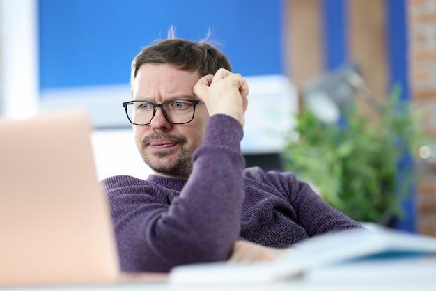 Homme Mécontent Avec Des Lunettes En Regardant L'écran Du Portable. Problèmes Au Concept De Travail Photo Premium