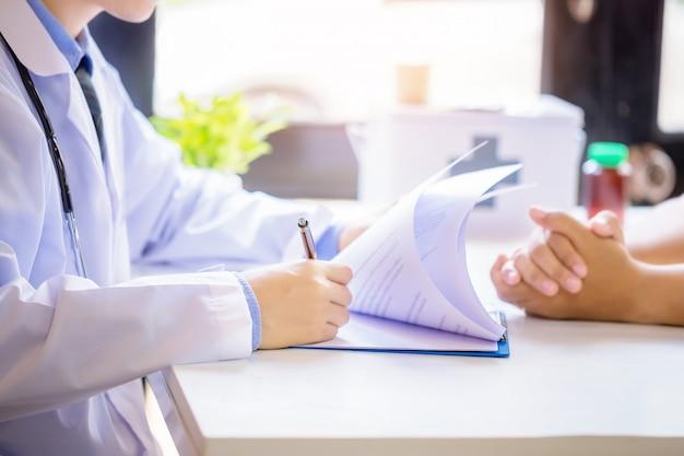 Homme Médecin Consultant Un Patient Alors Qu'il Remplissait Un Formulaire De Demande Au Bureau De L'hôpital. Photo gratuit