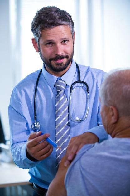 Homme médecin donnant une injection à un patient à l'hôpital Photo gratuit