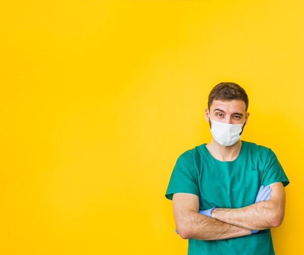 Homme médecin en masque avec les bras croisés Photo gratuit