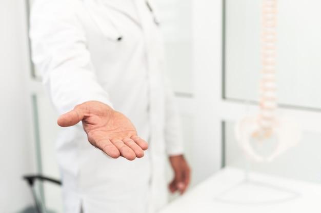 Homme médecin offrant sa main Photo gratuit