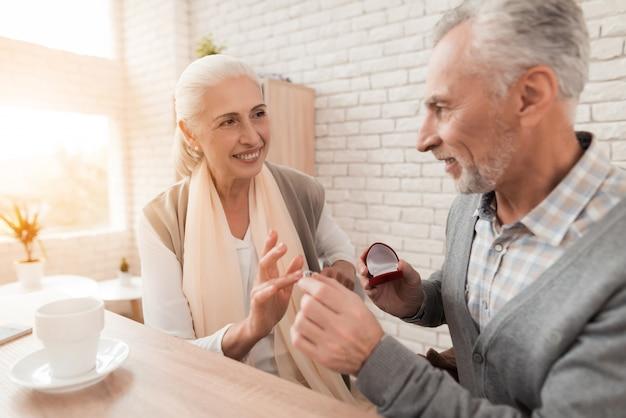 L'homme met la bague de fiançailles sous la main d'une femme mature. Photo Premium