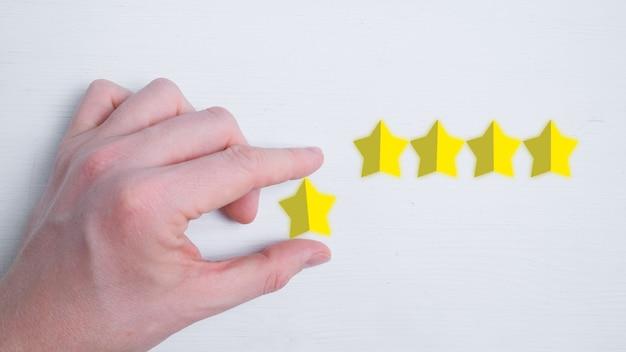Un Homme Met Une Note Abstraite De Cinq étoiles Sur Un Blanc. Meilleur Score. Mise à Plat. Photo Premium
