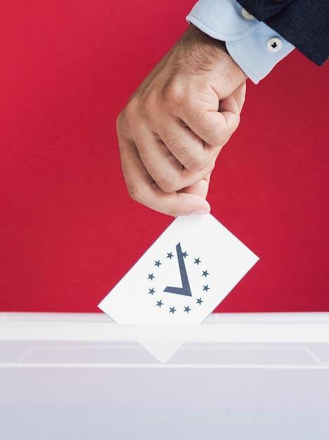 Homme mettant un bulletin de vote dans une boîte avec un fond rouge Photo gratuit