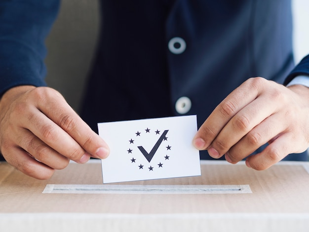 Homme mettant un bulletin de vote dans une boîte Photo gratuit