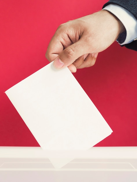 Homme mettant un bulletin de vote vide dans une boîte de maquette Photo gratuit
