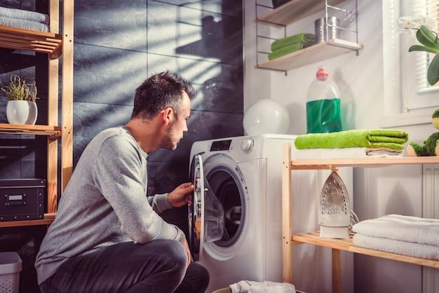 Homme mettant des vêtements dans une machine à laver Photo Premium